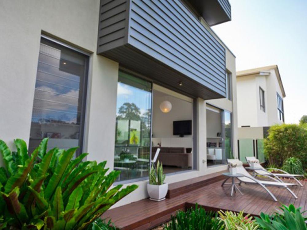 Terraza acristalada con perfiles de aluminio para acceso al jardín